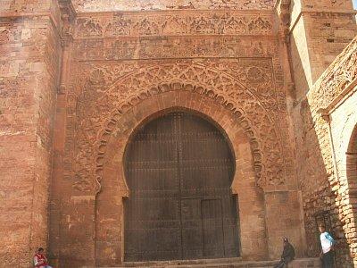 """Bab Oudaia - Výzdoba brány je založena na typicky islámském rytmu, který vytváří napětí mezi překypujícím rozpětím oblouků a těžkým ohraničujícím obdélníkem samotné brány. Základní prvek brány tvoří pochipitelně oblouk, který se v tomto případě představuje sled tří, postupně stále zdobenějších oblouků. Po prvním - prosté podkově - následují dva bohatě zdobené. Ten vnější je vyzdoben typicky almohadským motivem darj w ktarf (motiv \""""tváře a ramene\""""). Na vršku tento vzor rámuje pruh geometrických ornamentů, které se jeví dost nahodile, ale při pozorném pohledu vytvářejí dojem pohybu a pokračování mimo bránu.  (nahrál: Petr Kubík)"""